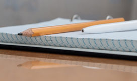 Pen, pencil, book and notebook lying on the desk. Written on a yellow wooden table lay a pen notebook and pencil book Stock Photo