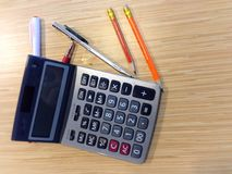 Pen,pencil and calculator on wooden surface Stock Photo