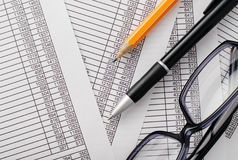 Pen, Pencil and Eyeglasses on Top of Reports Royalty Free Stock Photo