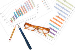 Pen and pencil with glasses on graph background. Royalty Free Stock Photo