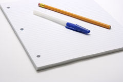 Pen and Pencil on lined paper. Blue capped pen and yellow pencil on blue lined and three hole punched paper for offices, businesses or back to school time royalty free stock photos