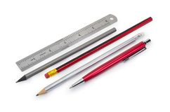 Pen, pencils and measuring ruler in inches. Pen, several pencils and stainless steel measuring ruler in inches on a white background royalty free stock images