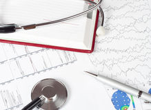 Pen and phonendoscope. Silver pen and stethoscope lying on a chart Royalty Free Stock Images