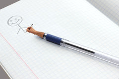 Pen picture. Pen draws a person in a notebook Royalty Free Stock Photo