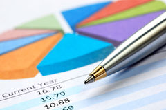Pen on Pie Chart. Silver ballpoint pen on pie chart with financial figures Royalty Free Stock Image