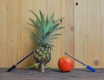 Pen-Pineapple-Apple-Pen on wooden background. Stock Photo