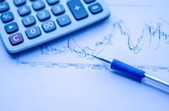 Pen placed over financial statistics and charts Stock Images