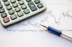 Pen placed over financial statistics and charts Royalty Free Stock Images