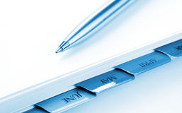 Pen on Planner. Silver ballpoint pen on a day planner file.  Soft focus on pen point.  Blue tone Stock Photography