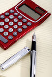 Pen and pocket calculator lying on a sheet Stock Image