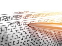 Pen point on the time sheet report with light flare Royalty Free Stock Image
