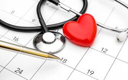 Pen pointing on calendar with stethoscope and red heart. Date for medical examiner