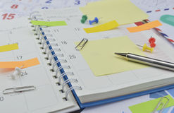 Pen with post It notes and pin on business diary page Royalty Free Stock Photography