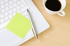 Pen with postit note, laptop and cup of coffee. Pen with blank green postit note on white laptop keyboard arranged with cup of coffee Royalty Free Stock Photo