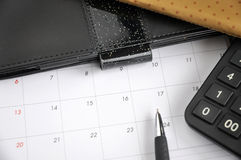 Pen put on calendar. With calculator and organizer book Royalty Free Stock Image