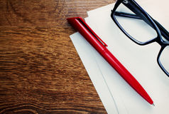 Pen and reading glasses on blank paper Royalty Free Stock Photo