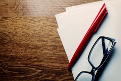 Pen and reading glasses on blank paper Stock Images