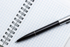 A pen rests on a notepad Royalty Free Stock Images