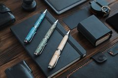 Pen set luxury. A set of expensive collectible pens made of wood. Raskladka accessories, glasses, watches, knives, compass, note book, wooden background Stock Photography