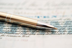 Pen on shares. Close up of pen on ten shares Royalty Free Stock Photo