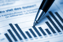 Pen showing diagram on financial report. /magazine (blue tone version Stock Image