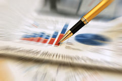 Pen showing diagram on financial report. /magazine Royalty Free Stock Photo