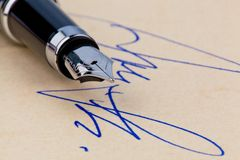 A pen and a signature. On yellow paper. Symbolic of closing deals Stock Photography