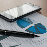 Pen, smartphone  on a background of  chart Stock Image