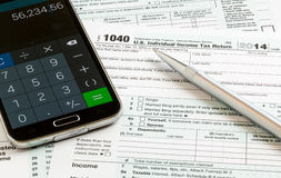 Pen and smartphone on 2014 form 1040 Royalty Free Stock Photos