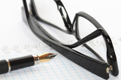 Pen And Spectacles. Closeup of fountain pen and  black spectacles lying on open spiral notebook Royalty Free Stock Photo