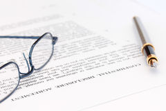 Pen and Spectacles with Disclosure Agreement. Fountain pen and blue spectacles resting on top of disclosure agreement Royalty Free Stock Image