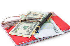 Pen, spectacles, dollar, euro. The pen, spectacles, dollars, euro are lying on a red notebook Stock Image