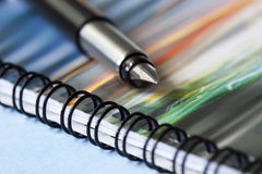 Pen on Spiral Notebook. Fountain pen on colorful spiral notebook. Focus on tip of pen Royalty Free Stock Image