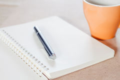 Pen and spiral notebook with coffee cup Stock Photo