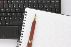 Pen and spiral notepad on black laptop keyboard Stock Photography