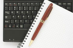 Pen and spiral notepad on laptop keyboard. Pen and spiral notepad on black laptop keyboard Stock Photo