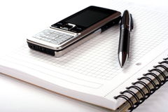 Pen, spiral notepad and mobile phone Royalty Free Stock Image