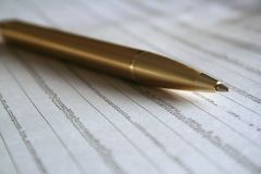 Pen and Statistics. A gold ballpoint pen on the business page of the newspaper Royalty Free Stock Photos
