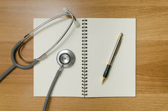 Pen and stethoscope on book Stock Images