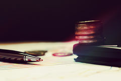 Pen on summary report and coin on calculator. Royalty Free Stock Photo