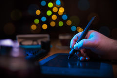 Pen tablet on the desk. Graphic designer holding a pen over tablet Royalty Free Stock Photo