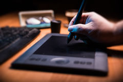 Pen tablet on the desk. Graphic designer holding a pen over tablet Royalty Free Stock Images