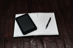 A Pen and Tablet on Open Blank Notebook on Wooden Background. Business Concept. Selective Focus. Top View Stock Image