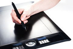 Pen tablet with pen in hand. Painting with a digital tablet Royalty Free Stock Photo