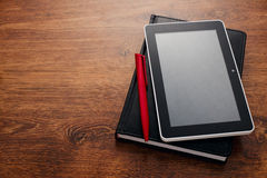 Pen and Tablet on Top of Closed Book at the Table Stock Images