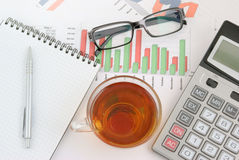 Pen, tea and calculator on paper table Stock Photos