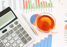 Pen, tea and calculator on paper table Royalty Free Stock Images