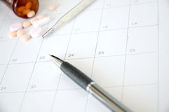 Pen and thermometer on schedule Royalty Free Stock Photos