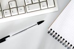 Pen, toetsenbord en notitieboekjeclose-up stock fotografie