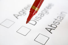 Pen on top 'Disagree' checkbox. Red pen is about to choose 'Disagree', placed on top of the checkbox. Focus on the pen. There is soft vignette around the corner Royalty Free Stock Photos